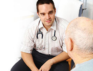 Male doctor talking to elderly patient
